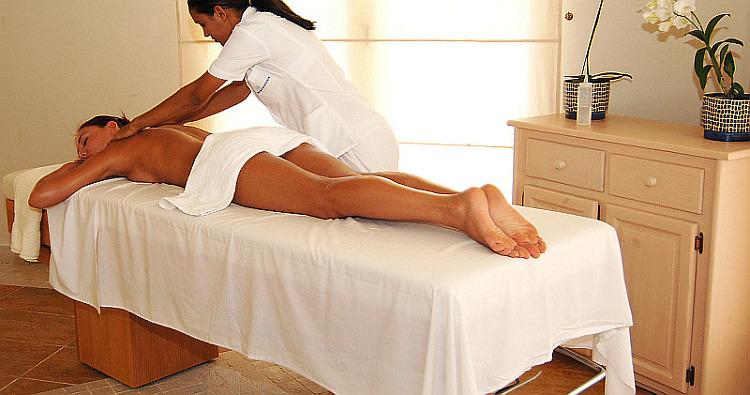massage therapist working client in spa